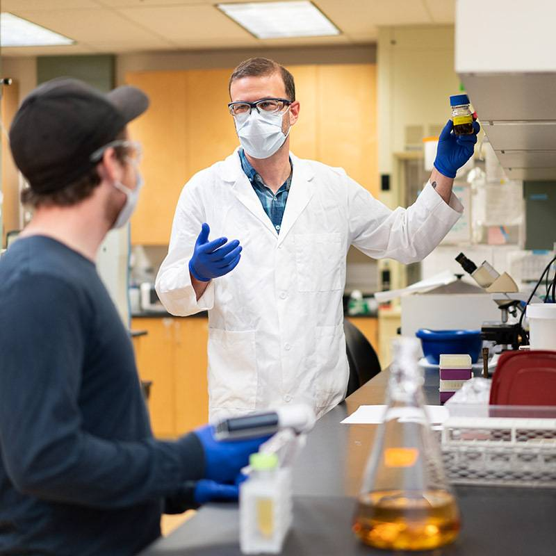 A professor wearing lab gear shows a beaker of liquid to a student.
